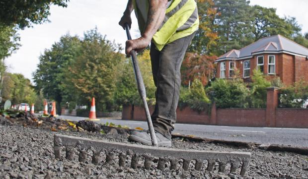 Raking whilst resurfacing a footway